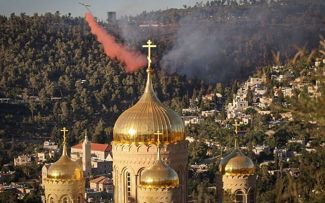 A firefighting plane tries to extinguish a large brush fire behind the the Russian Church in the Jerusalem neighborhood of Ein Kerem, Wednesday, June 25, 2014. (photo credit: Flash90)