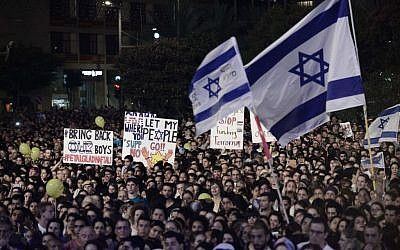 Israelis hold signs during a rally calling for the release of of three kidnapped teenagers -- Eyal Yifrach, Gil-ad Shaar and Naftali Fraenkel -- in Tel Aviv, Sunday, June 29, 2014. (Photo credit: Tomer Neuberg/Flash90)