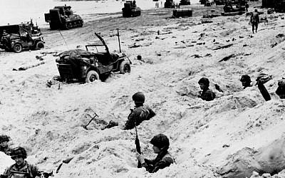 This June 6, 1944, file photo shows American soldiers of the Allied Expeditionary Force securing a beachhead during initial landing operations at Normandy, France. (AP Photo/Weston Haynes, File)