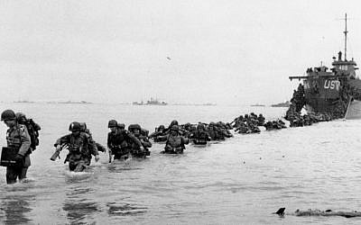 US reinforcements wade through the surf from a landing craft in the days following D-Day and the Allied invasion of Nazi-occupied France at Normandy in June 1944 during World War II. (AP Photo/Bert Brandt, File)