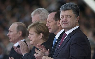 Ukraine's President-elect Petro Poroshenko, right, German Chancellor Angela Merkel, second left, and Russian President Vladimir Putin, left, applaud during the commemoration of the 70th anniversary of the D-Day in Ouistreham, western France, Friday, June 6, 2014. (photo credit: AP/Alexander Zemlianichenko)