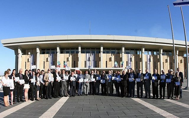 A delegation of European Jewish community leaders holds signs reading 'Bring back our boys' at the Knesset in Jerusalem on Wednesday, June 25, 2014 (photo credit: Yoel Balinko/ Israeli Jewish Congress)