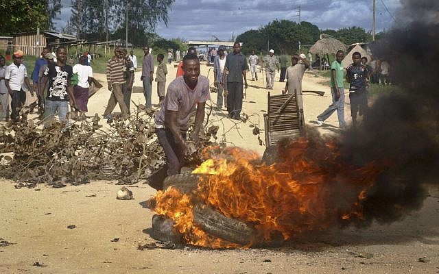 Residents barricade a road with burning tyres and other roadblocks as they protest against the recent killings and what they claimed was the government's failure to provide them with enough security, in the village of Kibaoni just outside the town of Mpeketoni, about 60 miles (100 kilometers) from the Somali border on the coast of Kenya Tuesday, June 17, 2014.  (photo credit: AP Photo)