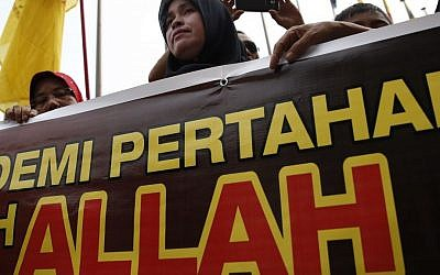 "A Muslim woman holds a banner reading ""Allah"" during a protest outside the Court of Appeal in Putrajaya, outside Kuala Lumpur, Malaysia, Monday, June 23, 2014. (AP Photo/Vincent Thian)"