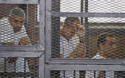 Mohammed Fahmy (left), Canadian-Egyptian acting bureau chief of al-Jazeera; Australian correspondent Peter Greste (center); and Egyptian producer Baher Mohamed in the defendant's cage during their trial on terror charges, Cairo, May 15, 2014. (photo credit: AP/Hamada Elrasam, File)