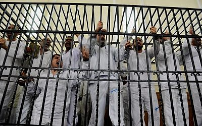 Supporters of Egypt's ousted president Mohammed Morsi charged with violence chant slogans against the Egyptian military during a trial in Alexandria, Egypt, on Saturday, March 29, 2014. (photo credit: AP/Heba Khamis/File)