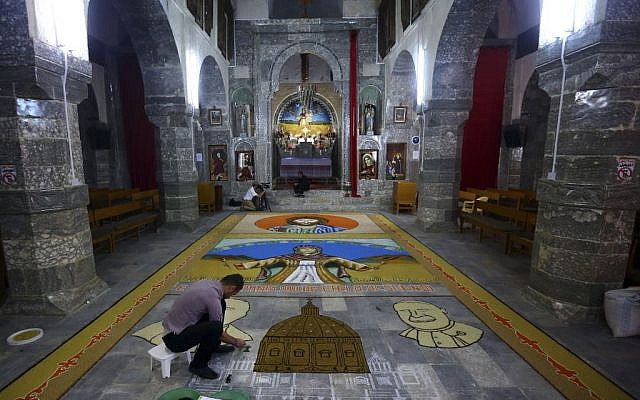 An Iraqi works on a temporary mosaic of Christian symbols made from the area's produce, including wheat, beans and lentils to commemorate an upcoming harvest feast, at the Chaldean Church of the Virgin Mary of the Harvest, in Alqosh,  June 15, 2014. (photo credit: AP)