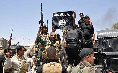 Iraqi security forces hold up a flag of the Islamic State in Iraq and the Levant they captured during an operation to regain control of Dallah Abbas north of Baqouba, 35 miles (60 kilometers) northeast of Baghdad, Iraq, June 28, 2014. (photo credit: AP)