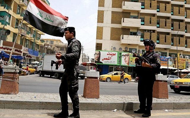 File: Iraqi federal policemen stand guard at a checkpoint in Baghdad, Iraq, Wednesday, June. 11, 2014. (AP/Karim Kadim)