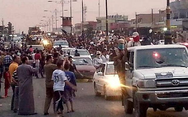 Militants parade down a main road in Mosul, Iraq, on Wednesday, June 11, 2014. (photo credit: AP/militant source via Twitter)