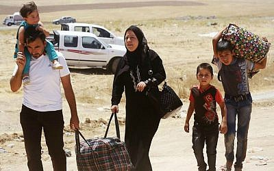 Iraqis who have fled the violence in their hometown of Mosul line arrive at Khazir refugee camp outside of Irbil, 217 miles (350 kilometers) north of Baghdad, Iraq, Monday, June 16, 2014. (AP Photo)