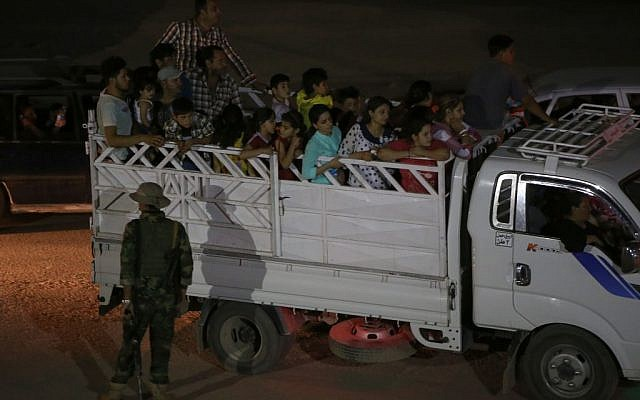 Fleeing Iraqi citizens from Mosul and other northern towns sit on a truck as they cross to secure areas at a Kurdish security forces checkpoint, in the Khazer area between the Iraqi city of Mosul and the Kurdish city of Irbil, northern Iraq, Wednesday June 25, 2014. (photo credit: AP Photo/Hussein Malla)