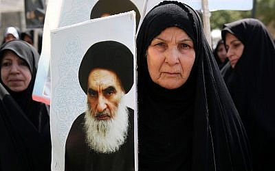 An Iraqi woman living in Iran holds a poster of the Grand Ayatollah Ali al-Sistani, Iraq's top Shi'ite cleric, in a demonstration against Sunni militants of the al-Qaeda-inspired Islamic State of Iraq and the Levant, or ISIL, and to support Ayatollah al-Sistani, in Tehran, Iran. (photo credit: AP/Ebrahim Noroozi)