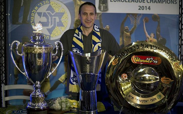Maccabi Tel Aviv's former head coach David Blatt poses for photographers with the Israeli cup, European club champions cup and the Israeli club champions trophy after a news conference in Tel Aviv, Israel,Thursday, June 12, 2014. (photo credit: AP/Ariel Schalit)