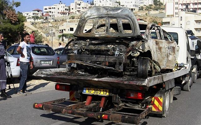 The burnt Hyundai believed used by the kidnappers and killers of three Israeli teenagers is taken away near Hebron, Friday, June 13, 2014. (photo credit: AP/Nasser Shiyoukhi)