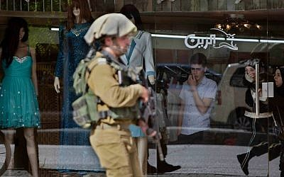 An IDF soldier walks on a street in a market in an attempt to obtain security camera footage during a search for three missing Israeli teens believed to have been abducted, while scouring the West Bank city of Hebron on Thursday, June 19, 2014. (AP Photo/Majdi Mohammed)