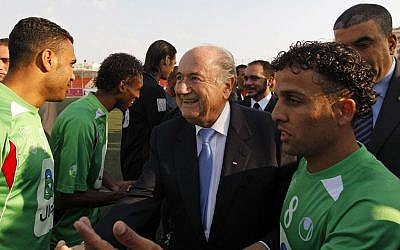 FIFA president Joseph S. Blatter, center, greets members of the Palestinian refugee camp team from Amari before their friendly match against the Senegalese club team Dakar, in the West Bank town of Aram, near Ramallah. May 15, 2011 (photo credit: May 15, 2011)
