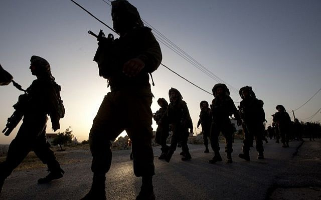 Israeli soldiers patrol during a military operation to search for three missing teenagers outside the West Bank city of Hebron, Monday, June 16, 2014. (Photo credit: AP/Majdi Mohammed)