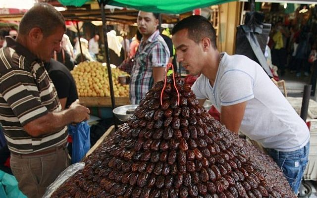 A Palestinian vendor sells dates for Ramadan at a market in Jenin, June 28, 2014. (photo credit: AP/Mohammed Ballas)