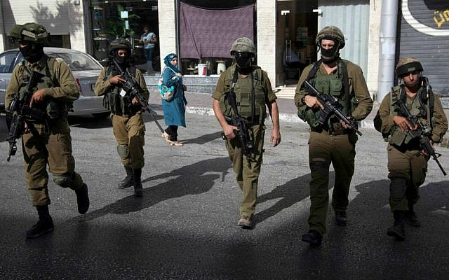 Illustrative photo of IDF soldiers walking on a street in the West Bank city of Hebron, June 19, 2014. (AP/Majdi Mohammed)