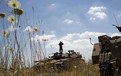 Israeli soldiers work on their tank following the first death on the Israeli side of the Golan since the Syrian civil war erupted more than three years ago, near the Israeli village of Alonei Habashan, close to the Quneitra border crossing, Sunday, June 22, 2014. (AP Photo/Oded Balilty)