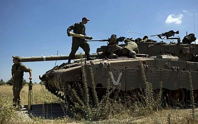 Israeli soldiers load shells into their tank following the first death on the Israeli side of the Golan since the eruption of the Syrian civil war more than three years ago, near the Israeli village of Alonei Habashan, June 22, 2014 (AP/Oded Balilty)