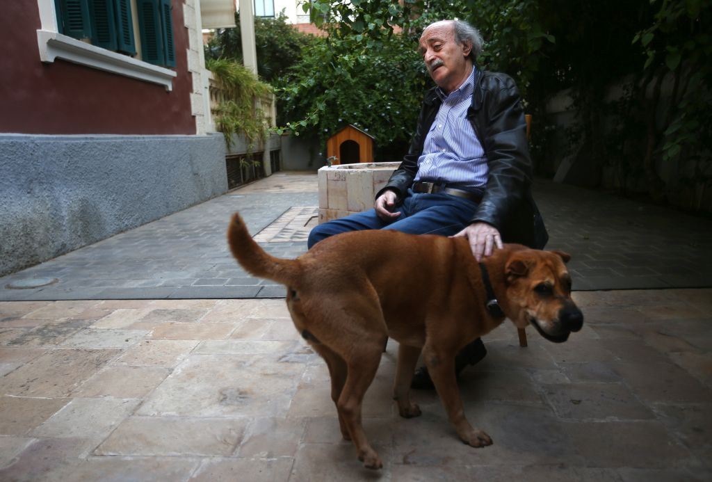 In this picture taken on May 28, 2014, Walid Jumblatt, the political leader of Lebanon's minority Druse sect, pets his dog Oscar at his garden house in Beirut, Lebanon. (photo credit: AP Photo/Hussein Malla)