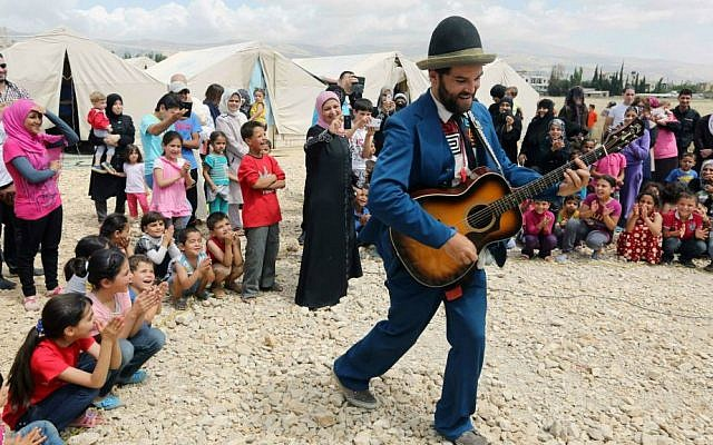 """In this June 6, 2014 photo, American clown David Clay, a member of """"Clowns Without Borders,"""" performs for children at a Syrian refugee camp in the eastern town of Chtoura, in Bekaa valley, Lebanon. (AP Photo/Bilal Hussein)"""