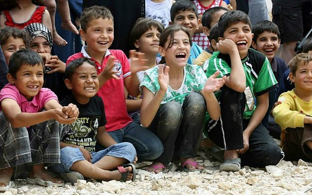 """In this June 6, 2014 photo, Syrian refugee children smile while watching members of """"Clowns Without Borders"""" perform at a Syrian refugee camp in the eastern town of Chtoura, in Bekaa valley, Lebanon. (AP Photo/Bilal Hussein)"""