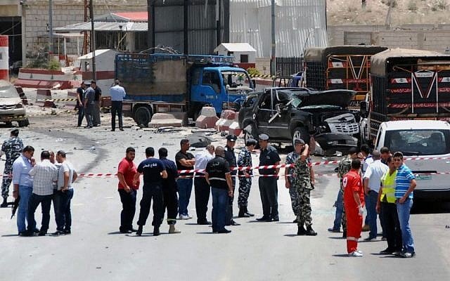 Lebanese army and plainclothes policemen gather at the site of an explosion near a police checkpoint in the eastern town of Dahr el-Baidar, Lebanon, Friday, June 20, 2014. (Photo credit: AP)