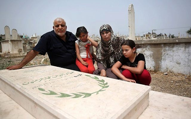 In this June 3, 2014, photo, Imad and Rawda Zanoun and their grandchildren Rawda and Farah visit the grave of the girls' father, Alaa Eldin, who was killed in a 2007 battle between Hamas and Fatah, days before the Hamas takeover in Gaza City. (photo credit: AP/Hatem Moussa)