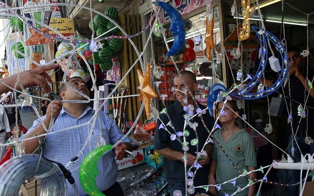 A Palestinian vendor displays decorations at a market ahead of Ramadan in the West Bank city of Jenin, June 28, 2014. (photo credit: AP/Mohammed Ballas)
