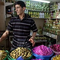 A Palestinian vendor displays food, including pickled vegetables and olives, in preparation for Ramadan at a market in the West Bank city of Hebron, Saturday, June 28, 2014. (photo credit: AP/Majdi Mohammed)
