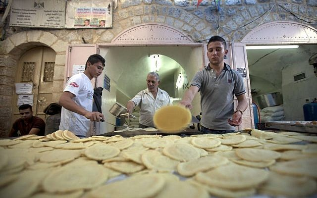 Palestinians workers makes pancakes, that are then filled with cheese or nuts and fried at home, in preparation for Ramadan at a market in the West Bank city of Hebron, Saturday, June 28, 2014. (photo credit: AP/Majdi Mohammed)