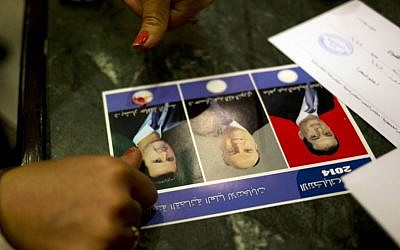 A woman votes for President Bashar Assad by marking the ballot with blood from her pricked finger, in Damascus, Syria, Tuesday June 3, 2014. (AP Photo/Dusan Vranic)