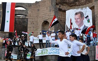 Supporters of Syrian President Bashar Assad hold his portraits and wave Syrian flags during a demonstration in support of his candidacy for presidential election in Suweida town, southern Syria, May 31 2014 (Photo credit: AP Photo/SANA)