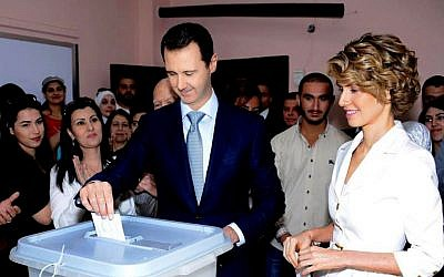 In this photo released on the official Facebook page of the Syrian Presidency, Syrian President Bashar Assad, center, casts his vote as Syrian first lady Asma Assad, right, stands next to him at a polling station, in Damascus, Syria, Tuesday, June 3, 2014. (photo credit: AP/Syrian Presidency via Facebook)