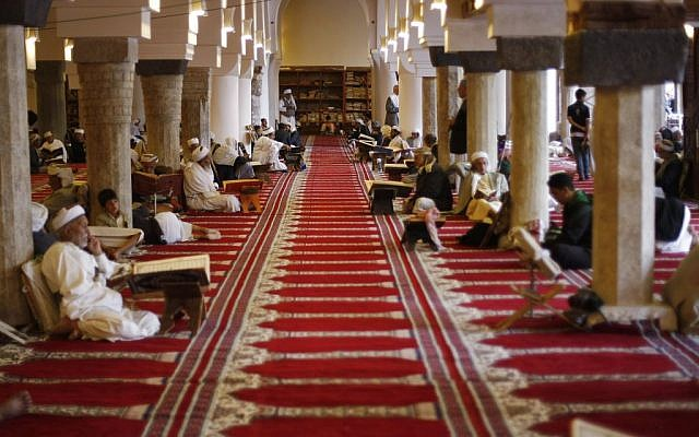Yemeni men read verses of the Quran, Islam's holy book, on the first day of the holy month of Ramadan in the Grand Mosque in the Old City of Sanaa, Yemen, Saturday, June 28, 2014. (photo credit: AP/Hani Mohammed)