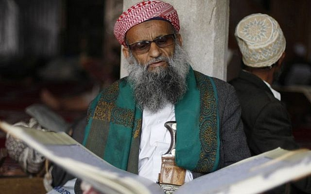 An elderly man reads verses of the Quran, Islam's holy book, on the first day of the holy month of Ramadan in the Grand Mosque in the Old City of Sanaa, Yemen, Saturday, June 28, 2014. (photo credit: AP/Hani Mohammed)