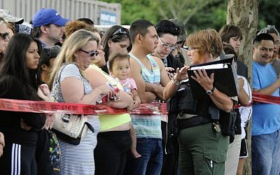 A police officer explains to parents how they are to be reunited as students arrive by bus at a shopping center parking lot in Wood Village, Ore., after a shooting at Reynolds High School Tuesday, June 10, 2014, in nearby Troutdale. (photo credit: AP/Greg Wahl-Stephens)