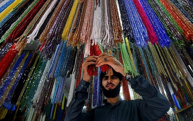 A Pakistani vendor arranges praying beads which worshippers buy for Islamic holy month of Ramadan in Peshawar, Pakistan, Saturday, July 28, 2014. (photo credit: AP/Mohammad Sajjad)