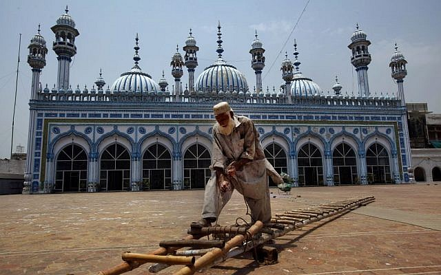 A painter fixes a ladder to whitewash the outer wall of a mosque in preparation for upcoming Islamic holy month of Ramadan in Rawalpindi, Pakistan, Saturday, July 28, 2014. (photo credit: AP/Anjum Naveed)