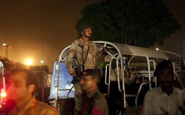 Pakistani security troops rush to Karachi airport terminal following attacks by unknown gunmen on Sunday night, June 8, 2014, in Pakistan. (Photo credit: AP/Shakil Adil)