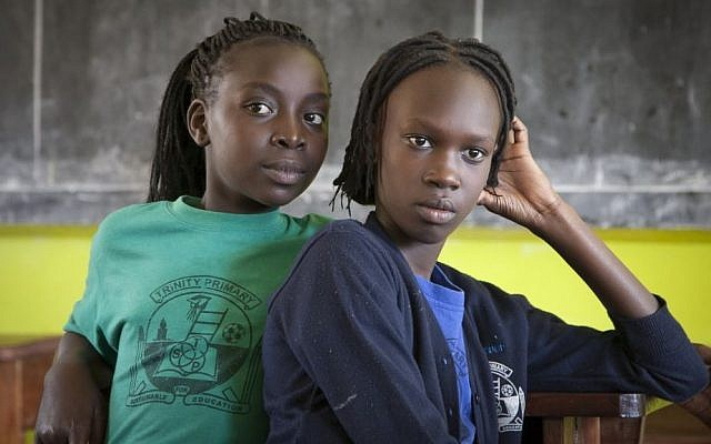 Two South Sudanese teenagers who previously lived in Israel listen to their friends reminisce about their time in Tel Aviv, in a classroom at the Trinity boarding school where they now live in Kampala, Uganda, April 9, 2014. (AP Photo/Rebecca Vassie)