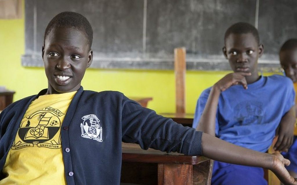 South Sudanese teenager Asunta Atoch, 16, left, who previously lived in Israel listens to her friends talk about their time in the country, in a classroom at the Trinity boarding school where they now live in Kampala, Uganda, April 9, 2014. (AP Photo/Rebecca Vassie)