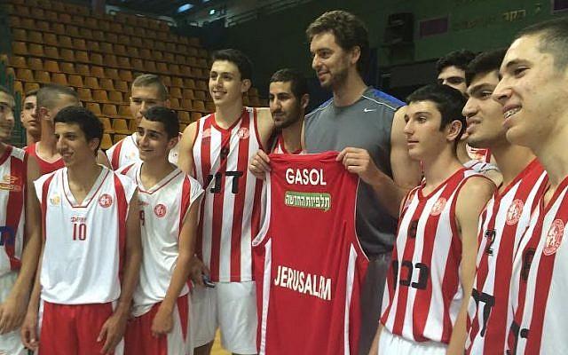 Pau Gasol holds up his new shirt at his Jerusalem basketball clinic, June 1, 2014 (photo credit- Raphael Gellar)