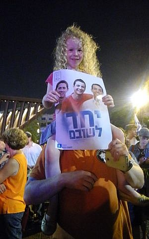 Six-year-old Uriya Noy, sitting on top of her father's shoulders at a rally on Sunday in Rabin Square (photo credit: Melanie Lidman/Times of Israel)