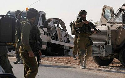 Israeli soldiers transport a burnt car which may have been connected to the disappearance of three teenagers near the West Bank city of Hebron, Friday, June 13, 2014 (photo credit: AP/Nasser Shiyoukhi)