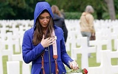 Marissa Neitling, 30, from Lake Oswego, Oregon, places a flower on a grave in the Normandy American Cemetery and Memorial, in Colleville sur Mer, France, Wednesday June 4, 2014. (photo credit: AP Photo/Claude Paris)