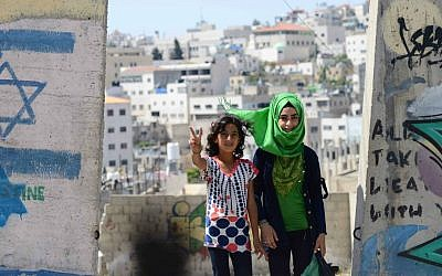 Young Arab children walk by a security wall painted with graffiti and and an Israeli flag, in the divided West Bank town of Hebron. June 24, 2014. (photo credit: Mendy Hechtman/FLASH90)